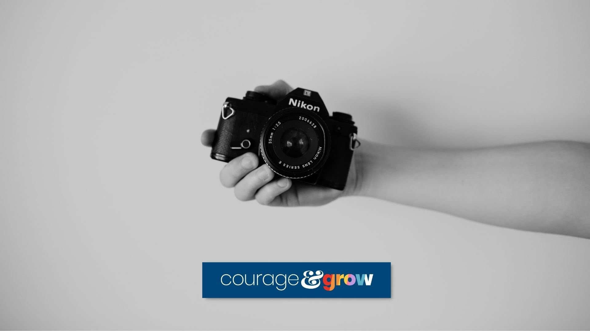 hand holding nikon camera with cg logo